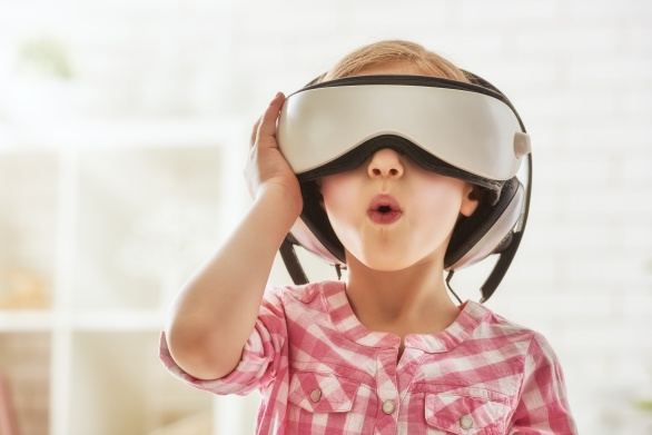 Cute little child girl playing game in virtual reality glasses.